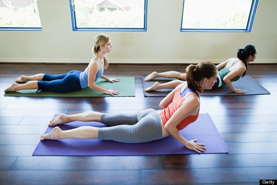 Three woman doing cobra pose in yoga class